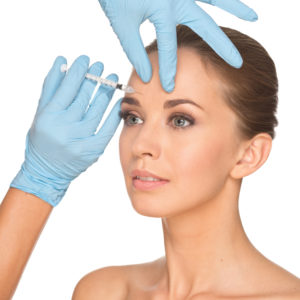 Attractive young woman gets cosmetic injection of botox, isolated over white background. Doctors hands making an injection in face. Beauty Treatment.